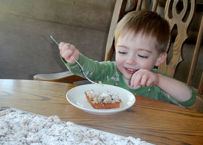 Little boy eating crumb cake