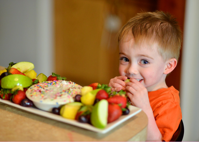 Boy eating fruit and yogurt dip